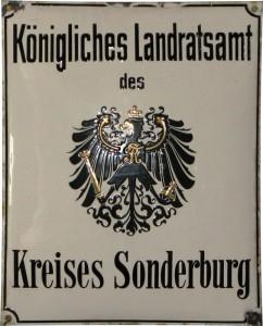 Embedsskilt fra den preussiske landråds bygning i Sønderborg Kreds Emaljeskilt fra: Museum Sønderjylland - Sønderborg Slot. Foto: Inge Adriansen